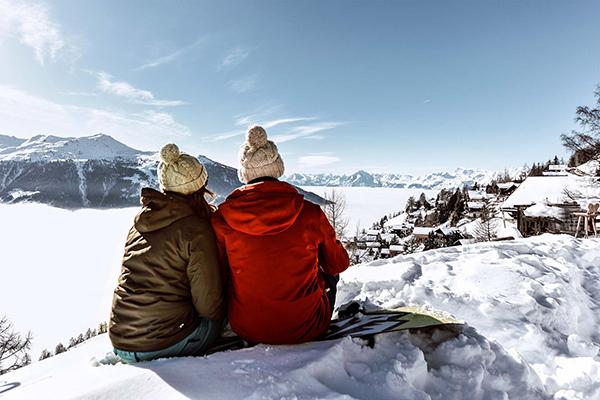 זוג יושב ומביט בהרים בשלג