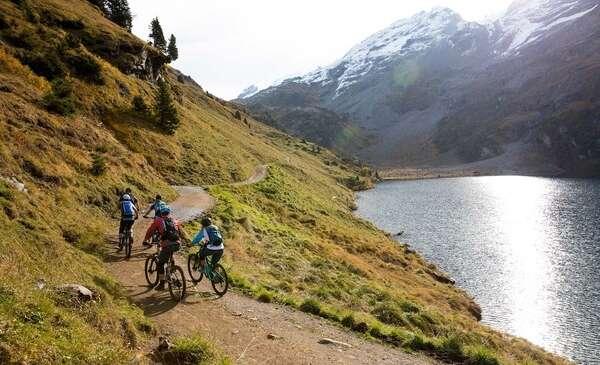 רוכבים חולפים על פני אגם בהרים