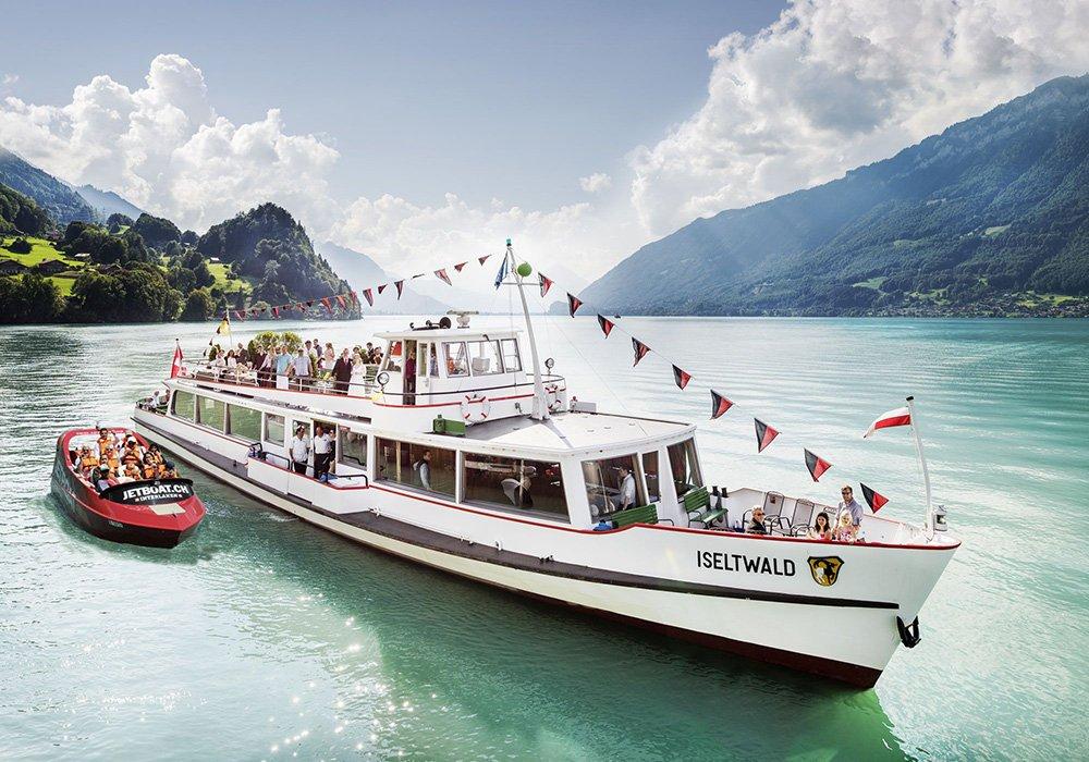 סירת jetboat לצד ספינת נוסעים באגם ברינץ