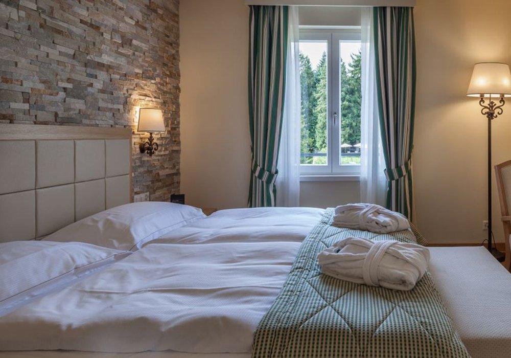 חדר שינה ומיטה במלון קורהאוס קדמריו בלוגאנו
