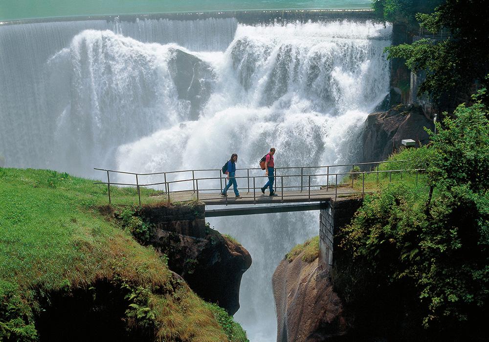 מטיילים על גשר עץ מעל נהר רוס