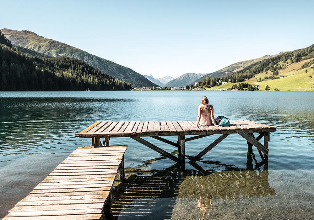 אישה יושבת על מזח על שפת אגם ואדוז