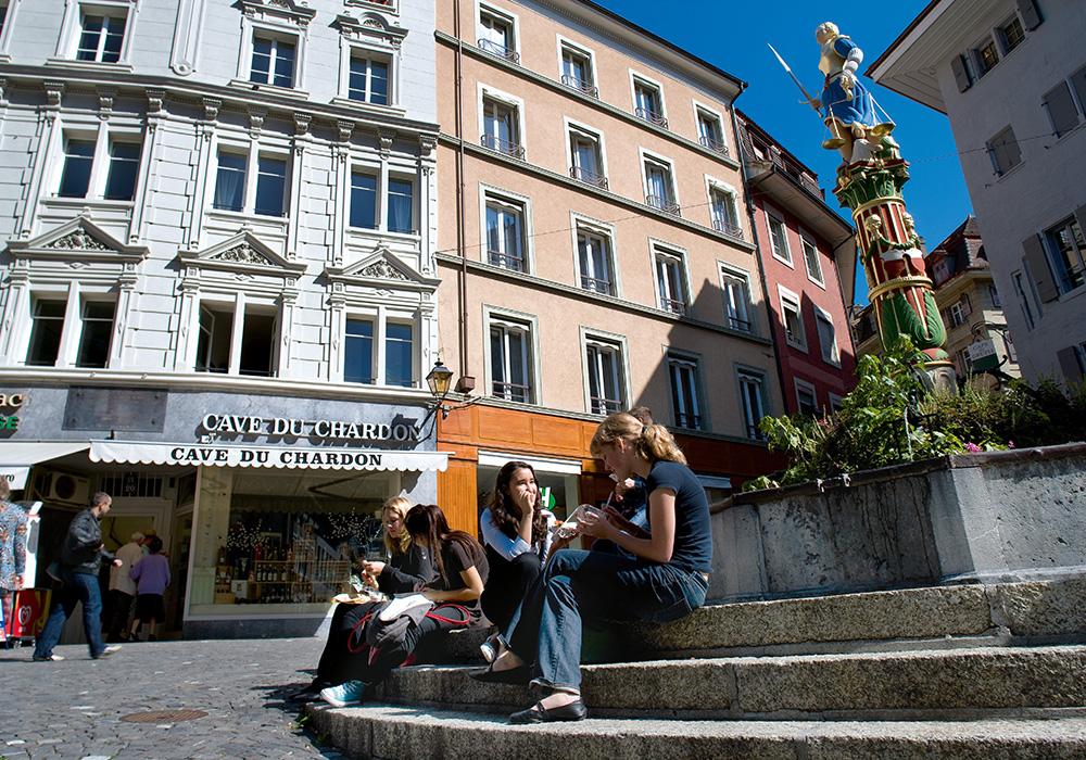 נשים יושבות על המדרגות ברובע העתיק של לוזאן