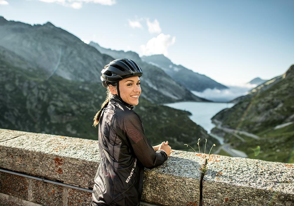 אישה מביטה בנהר ובהרים מגשר אבן