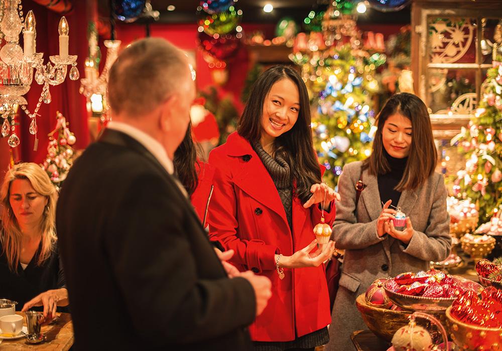 קניות בדוכן קישוטים בשוק חג המולד בבאזל